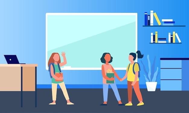 Schulmädchen treffen sich im klassenzimmer. gruppe von freunden, klassenkameraden, die hände halten und hallo flache vektorillustration winken. kommunikation, freundschaftskonzept Kostenlosen Vektoren