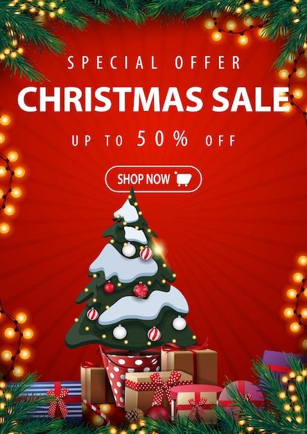 Sonderangebot, weihnachtsverkauf, bis zu 50% rabatt, rote vertikale rabattfahne mit weihnachtsbaum in einem topf mit geschenken, rahmen aus weihnachtsbaumzweigen, girlanden und geschenken Premium Vektoren