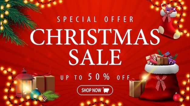 Sonderangebot, weihnachtsverkauf, bis zu 50% rabatt, rotes rabatt-banner mit girlande, weihnachtsbaumzweigen, weihnachtsstrumpf und roter weihnachtsmann-tasche mit geschenken Premium Vektoren