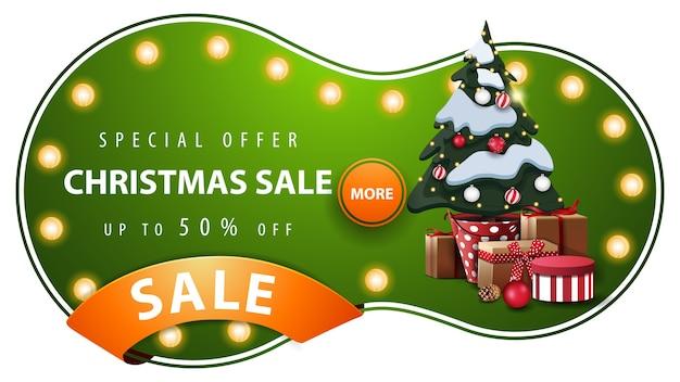 Sonderangebot, weihnachtsverkauf, grünes rabattbanner mit abstrakter runder form, glühbirnen, orangenband und weihnachtsbaum in einem topf mit geschenken Premium Vektoren