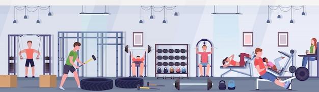 Sportliche leute, die übungen männer frauen, die zusammen an trainingsgeräten im fitnessstudio trainieren, trainieren gesunde lebensweise konzept modernen gesundheitsclub studio innen horizontale banner Premium Vektoren