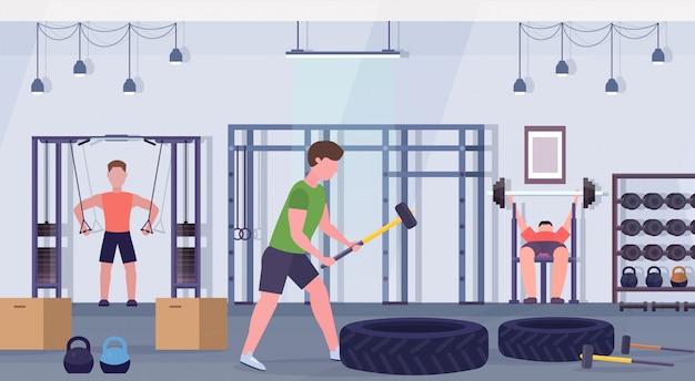 Sportliche leute, die übungen männer tun, die zusammen auf trainingsgeräten im fitnessstudio crossfit workout gesunden lebensstil konzept modernen health club studio interieur horizontal trainieren Premium Vektoren