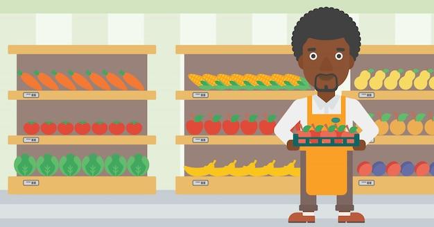 Supermarktarbeitskraft mit dem kasten voll von den äpfeln. Premium Vektoren