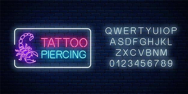 Tattoo und piercing salon glühendes neonschild mit skorpionemblem und alphabet. Premium Vektoren
