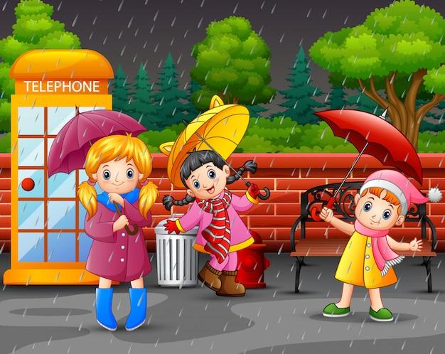 Tragender regenschirm des mädchens der karikatur drei Premium Vektoren