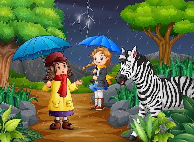 Tragender regenschirm mit zwei mädchen geht unter einen regen mit zebra Premium Vektoren