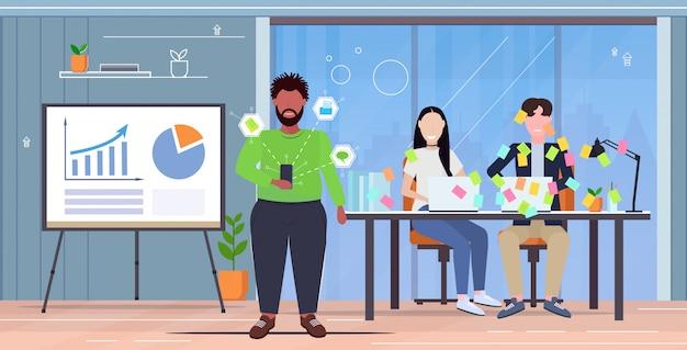 Überarbeiteter manager, der kollegen, die mit haftnotizen bedeckt sind, neue strategie erklärt geschäftsplanung teamarbeit präsentationskonzept modernes bürointerieur horizontal in voller länge Premium Vektoren