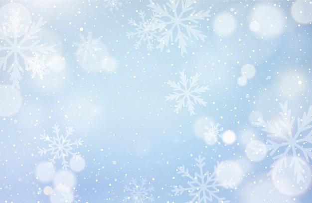 Unfokussierter winterhintergrund mit schneeflocken Kostenlosen Vektoren