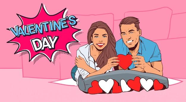 Valentine dat retro design-glückliches paar-griff-rotes herz, das auf bett-comic-art liegt Premium Vektoren