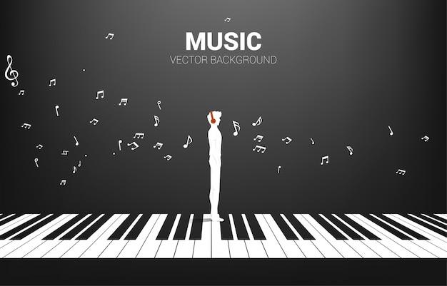 Vektorsilhouette des mannes, der mit klavierschlüssel mit fliegender musiknote steht. konzept hintergrund klaviermusik und erholung. Premium Vektoren