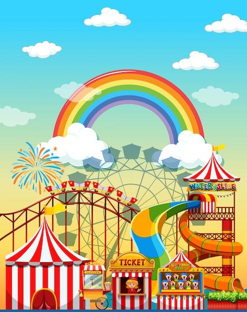 Vergnügungsparkszene am tag mit regenbogen im himmel Kostenlosen Vektoren