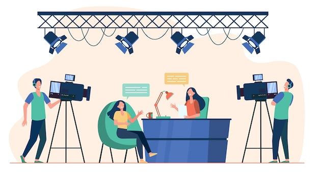 Videografen drehen interview im fernsehstudio. nachrichtenmoderator im gespräch mit dem gast der tv-show. flache vektorillustration für kamerateam, rundfunk, fernsehkonzept Kostenlosen Vektoren