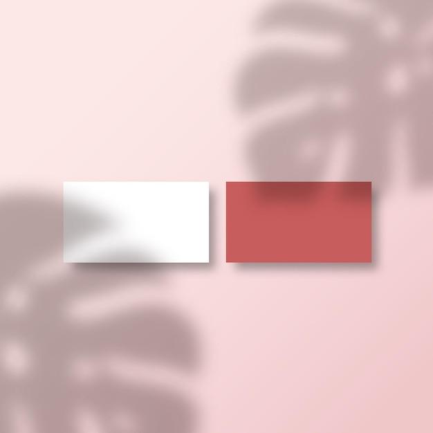 Visitenkarten auf einer oberfläche mit einem tropischen monstera palm leaves shadow overlay Premium Vektoren