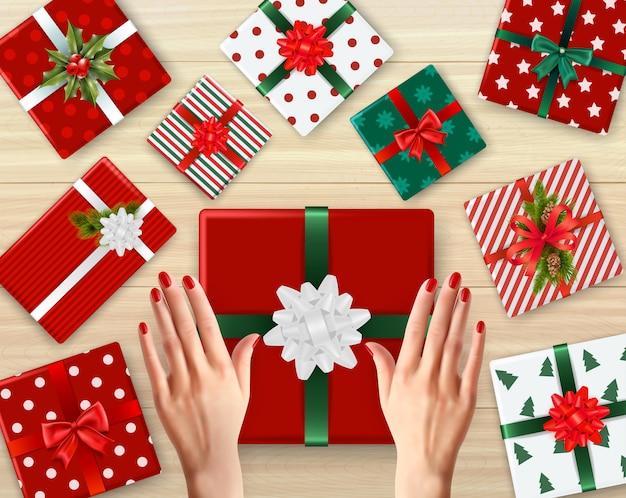 Weibliche hände und verzierte geschenkboxen aus pappe mit realistischem hintergrund unterschiedlicher farbe Kostenlosen Vektoren