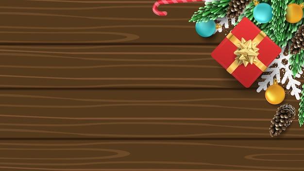Weihnachten 3d hintergrund mit geschenkbox, kiefer, ball, süßigkeiten und schneeflocke auf holz Premium Vektoren