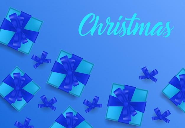 Weihnachtsbeschriftung auf blauem hintergrund mit geschenkboxen Kostenlosen Vektoren