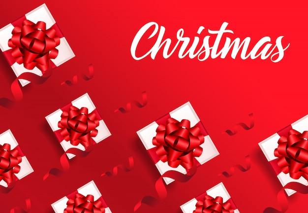Weihnachtsbeschriftung auf rotem hintergrund mit geschenkboxmuster Kostenlosen Vektoren