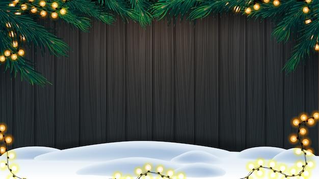 Weihnachtshintergrund, hölzerne wand mit rahmen von weihnachtsbaumasten, girlande und schnee auf boden Premium Vektoren