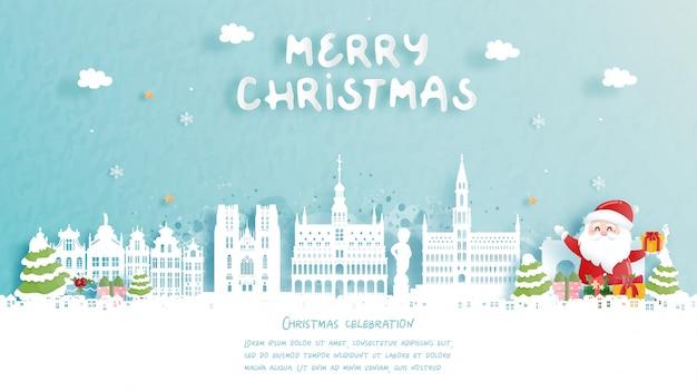 Weihnachtskarte mit reise nach belgien konzept. netter weihnachtsmann und geschenkboxen. weltberühmtes wahrzeichen in papierschnittartillustration. Premium Vektoren
