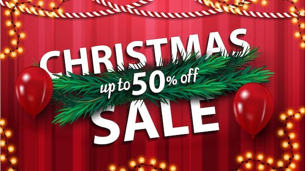 Weihnachtsverkauf, bis zu 50% rabatt, rote horizontale rabatt-banner mit weihnachtsbaum zweigen, luftballons und girlanden Premium Vektoren