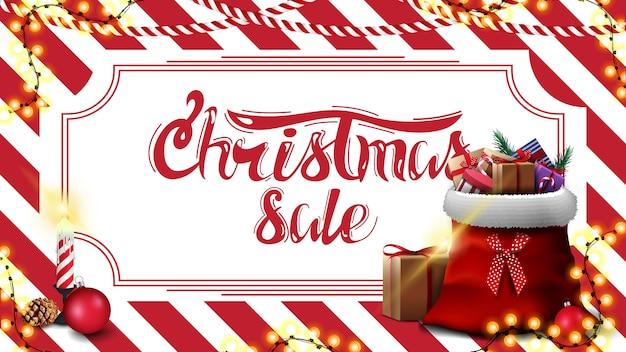 Weihnachtsverkauf, rabattfahne mit roter und weißer gestreifter beschaffenheit auf dem hintergrund und santa claus-tasche mit geschenken Premium Vektoren