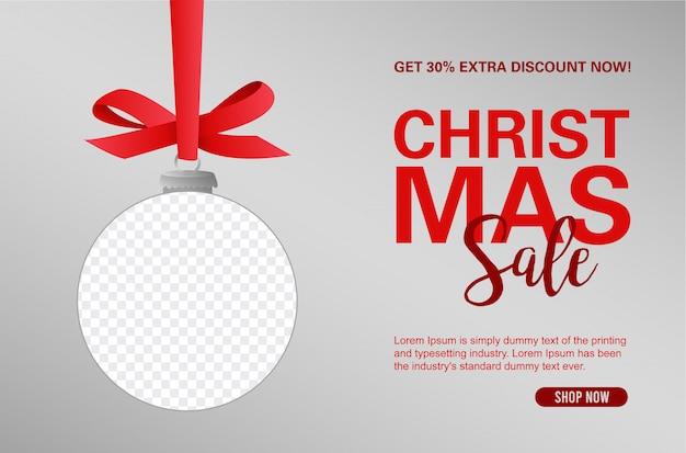 Weihnachtsverkaufs-fahnenhintergrund mit dem dekorativen ballhängen eines bandes mit rahmen Kostenlosen Vektoren