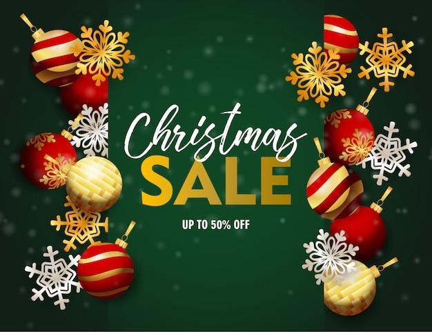 Weihnachtsverkaufsfahne mit bällen und flocken auf grünem boden Kostenlosen Vektoren