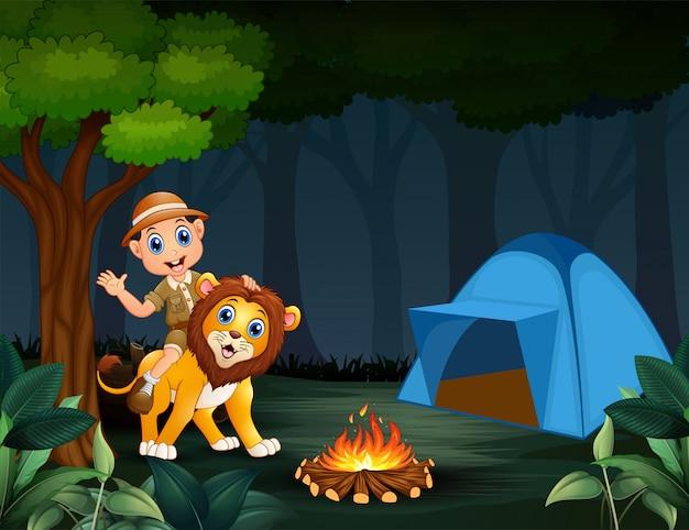 Zookeeper-junge und ein löwe im dschungel nachts Premium Vektoren