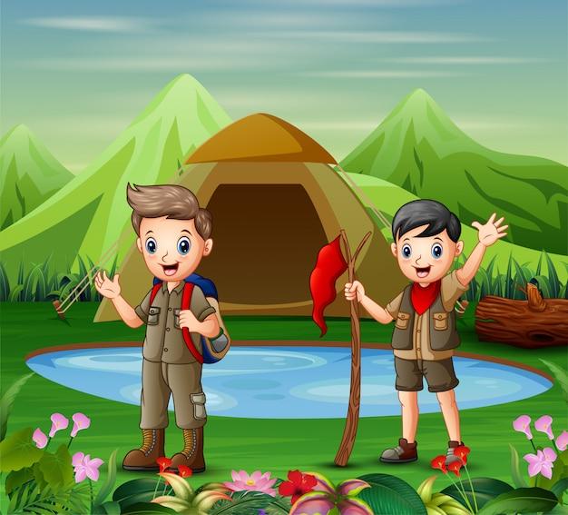 Zwei jungen in der kampierenden uniform eine natur erforschend Premium Vektoren