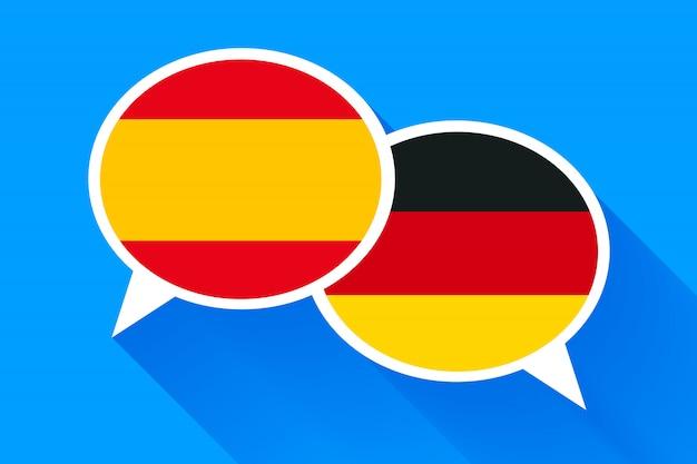 Zwei weiße sprechblasen mit spanien und deutschen flaggen. Premium Vektoren