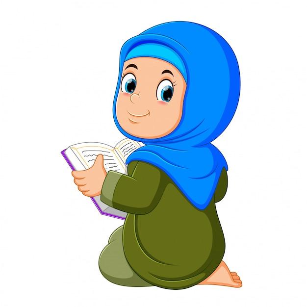 A linda garota com véu azul está segurando al quran Vetor Premium