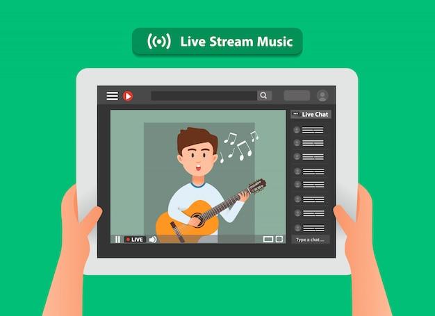 A mão de alguém segurando um tablet e assistindo música ao vivo on-line Vetor Premium