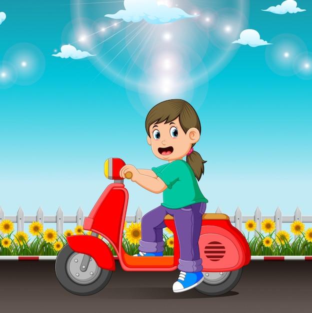 A menina está montando a scooter vermelha na estrada no dia Vetor Premium