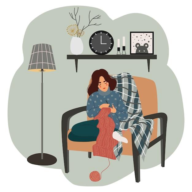 A menina senta-se em uma cadeira junto à lâmpada de assoalho e tricota no fundo da prateleira interior com um relógio, um vaso, uma foto e velas Vetor Premium