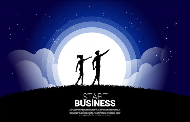 A silhueta da mulher de negócios e do homem de negócio aponta para a frente adiante na noite. conceito de missão de visão e empreendedor Vetor Premium