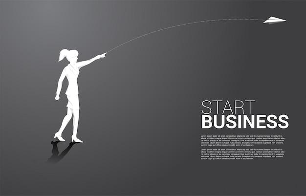 A silhueta da mulher de negócios joga para fora o avião de papel do origâmi. conceito de negócio de iniciar negócios e empresário Vetor Premium