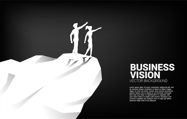 A silhueta do homem de negócios e da mulher de negócios aponta para a frente do penhasco da montanha. conceito de missão de visão de mercado de negócios start up Vetor Premium