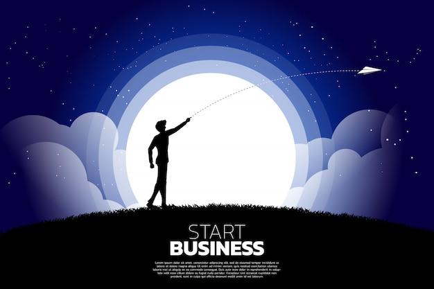 A silhueta do homem de negócios joga para fora o avião de papel do origâmi na noite. conceito de negócio de iniciar negócios e empresário Vetor Premium