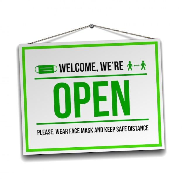 Abra o sinal na porta da frente - bem-vindo de volta. estamos trabalhando novamente. mantenha distância social e use máscara facial. isolado no branco Vetor Premium