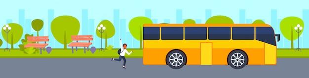Afro-americano adolescente adolescente apressar-se para ônibus escola conceito conceito estudante urbano acenar gesto mão mão urbano parque paisagem fundo horizontal Vetor Premium