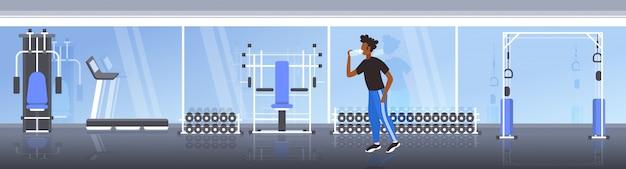 Afro-americano aptidão atleta homem beber água de garrafa de plástico após treino exercitar estilo de vida saudável conceito moderno ginásio interior horizontal comprimento total Vetor Premium