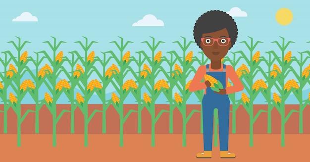 Agricultor segurando o milho Vetor Premium