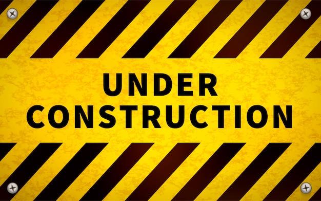 Amarelo sob o sinal de aviso de construção com parafusos de metal nos cantos Vetor Premium