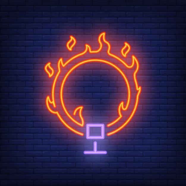 Anel no ícone de néon de fogo. aro flamejante do circo no fundo escuro da parede de tijolo. Vetor grátis