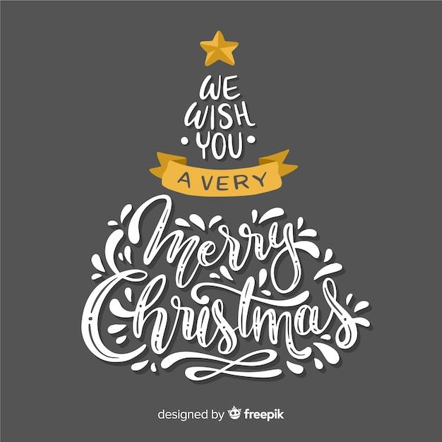 Árvore de natal com letras de feliz natal Vetor grátis
