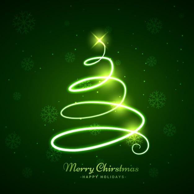 árvore de Natal de incandescência em fundo verde Vetor grátis