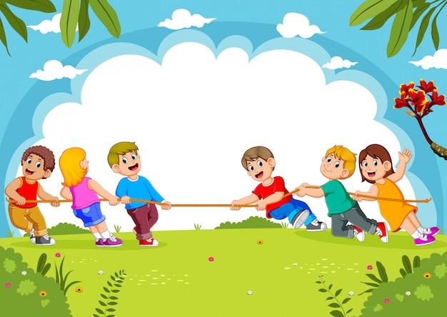 As crianças brincam de cabo de guerra no parque Vetor Premium