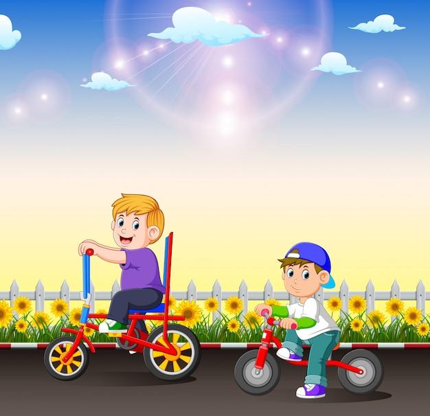 As duas crianças estão andando de bicicleta à tarde Vetor Premium