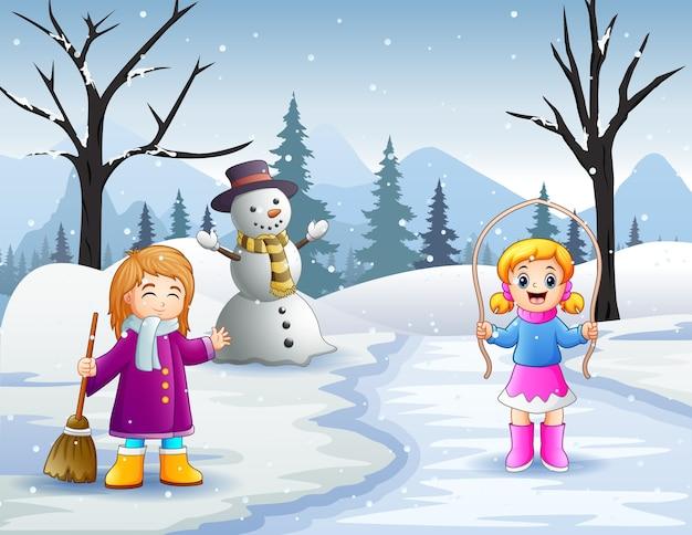 Atividade de duas meninas ao ar livre em paisagem de inverno com neve Vetor Premium