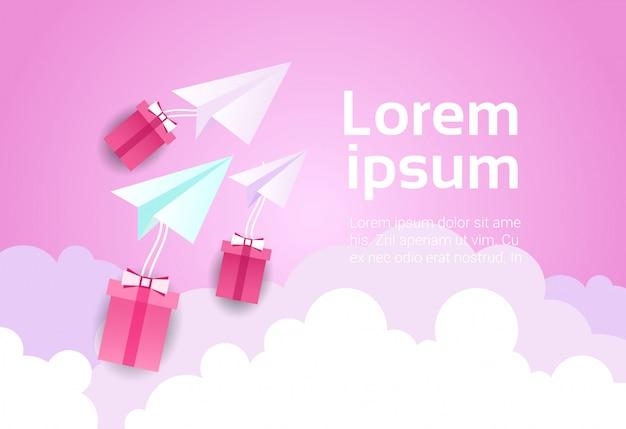 Avião de papel no céu sobre nuvens cor de rosa e caixas de presente Vetor Premium